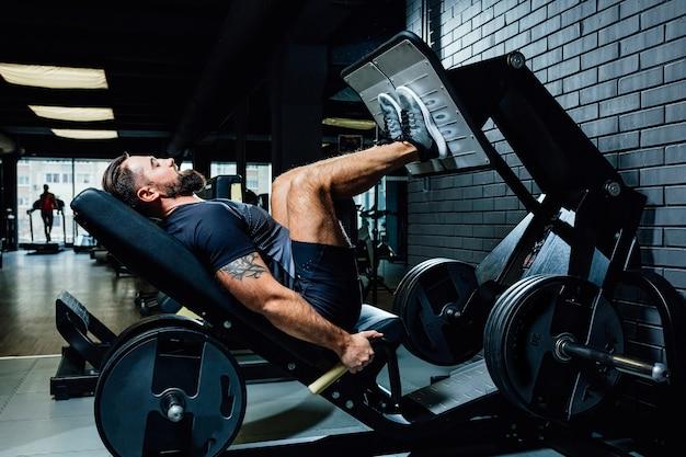 Brutale kaukasische gutaussehende fitnessmänner auf diät-trainingstrizeps im fitnessstudio, das bodybuilding-sportler aufpumpt