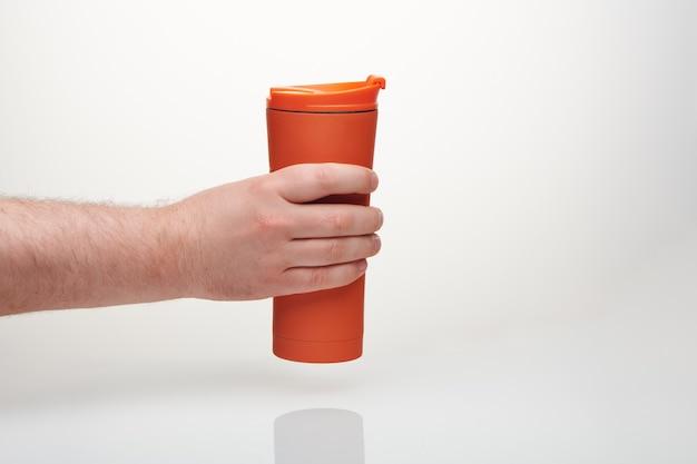 Brutale mannhand hält orange reisebecher. wiederverwendbare kaffeetasse zum mitnehmen. thermosflasche aus edelstahl mit schiebeverschluss. bechermodell für kalte und heiße getränke auf weißem hintergrund.