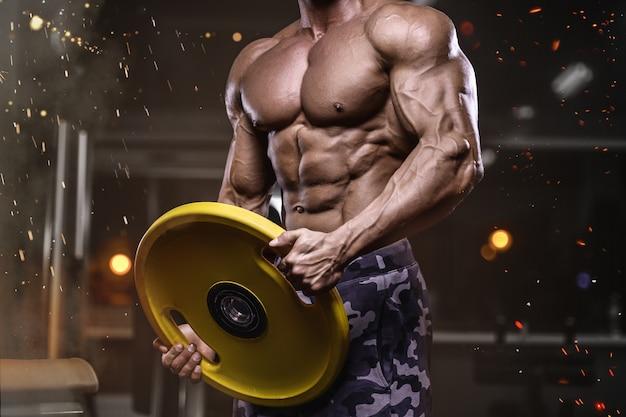 Brutale starke sportliche bodybuilder-männer, die muskeln mit hanteln aufpumpen