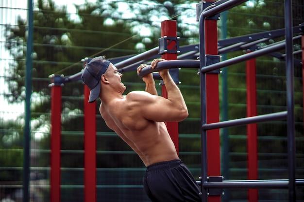 Brutaler athletischer mann, der klimmzugübungen auf einer querstange macht.