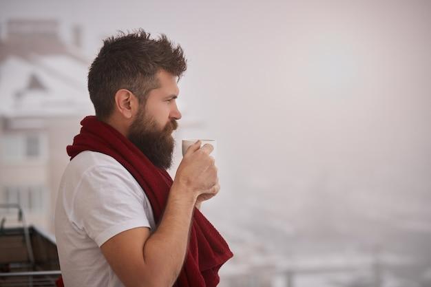 Brutaler bärtiger mann, der draußen mit rotem handtuch auf schultern steht und tasse mit dampfendem heißem getränk hält. junger hübscher sorgloser mann, der eine tasse kaffee genießt, während draußen schaut, guten morgen.