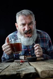 Brutaler grauhaariger erwachsener mann, der nach senfsteak und bier, feiertag, festival, oktoberfest oder st patrick tag verrückt ist