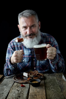 Brutaler grauhaariger erwachsener mann mit bart isst senfsteak und trinkt bier, einen feiertag, ein festival, ein oktoberfest oder einen st patrick tag