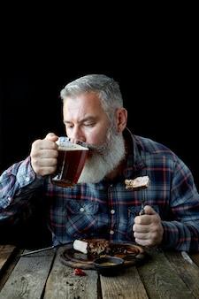 Brutaler grauhaariger erwachsener mann, verrückt nach senfsteak und bier