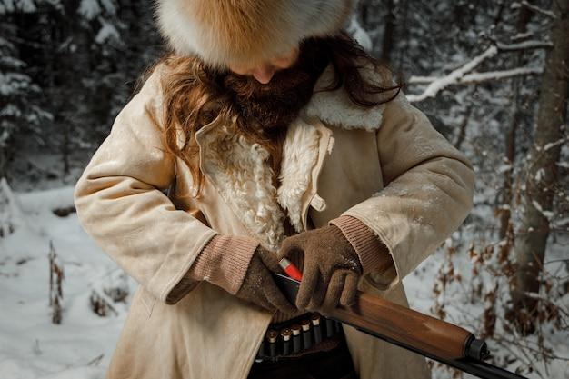 Brutaler jäger in winter vintage kleidung mit bart lädt munition in pistole