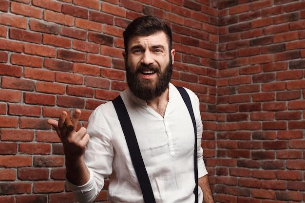 Brutaler junger hübscher mann, der zigarre auf ziegelmauer raucht.