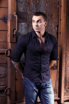 Brutaler junger sexueller mann im schwarzen hemd