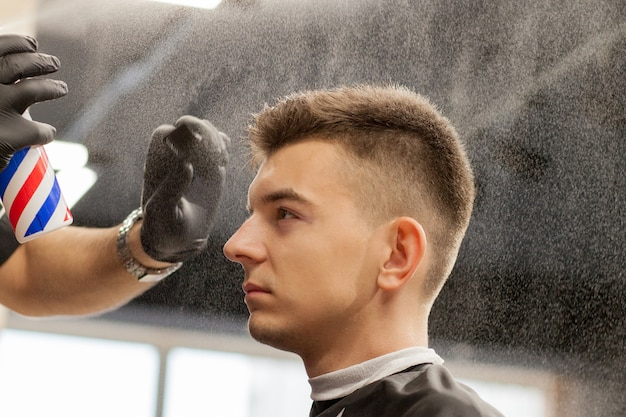 Brutaler kerl im modernen friseursalon. friseur macht frisur einen mann. meister friseur macht frisur mit haarschneidemaschine. konzept friseursalon