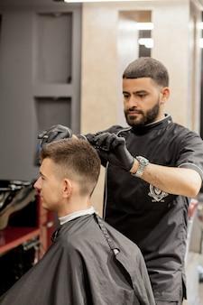 Brutaler kerl im modernen friseursalon. friseur macht frisur einen mann. meister friseur macht frisur mit haarschneider. friseur