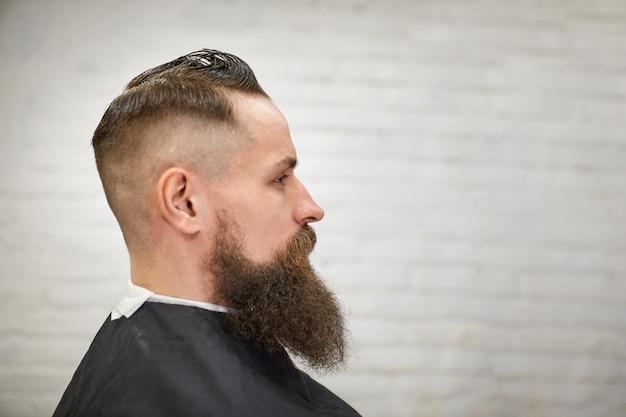 Brutaler kerl im modernen friseursalon. friseur macht frisur einen mann mit langem bart. meister friseur macht frisur mit haarschneider