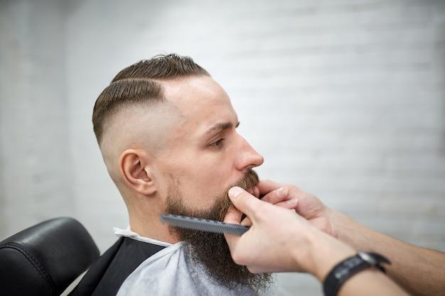 Brutaler kerl im modernen friseursalon. friseur macht frisur einen mann mit langem bart. meister friseur macht frisur mit schere und kamm