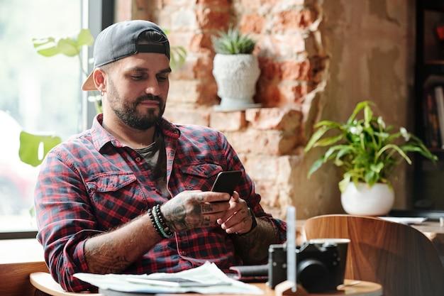Brutaler kerl in der ballkappe, der im gemütlichen café sitzt und sms auf smartphone liest, während stadtpause hat