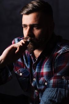 Brutaler mann, der elektronische zigarette raucht