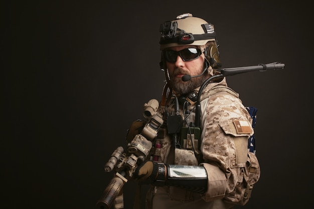 Brutaler mann in der militärischen wüstenuniform.