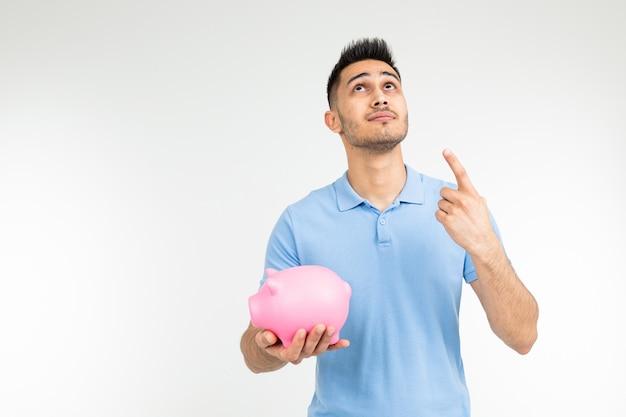 Brutaler mann in einem blauen t-shirt hält ein sparschwein und zeigt daumen auf das wachstum der geldeinsparungen auf einem weißen hintergrund mit kopienraum