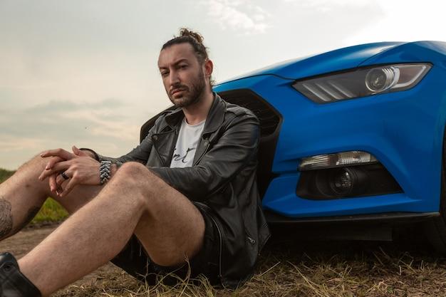 Brutaler mann in lederjacke sitzt auf hellblauem sportwagen in der mitte des feldes hochqualitatives foto gelehnt