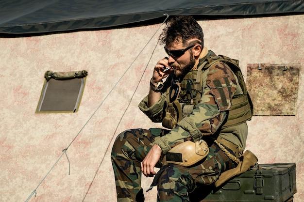 Brutaler mann mit sonnenbrille raucht zigarette gegen zelt im amerikanischen militärlager