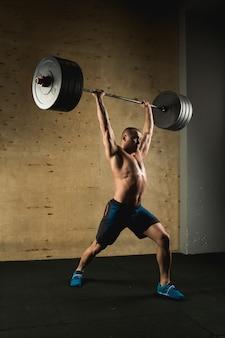 Brutaler muskulöser mann mit bartzug mit langhantel über kopf im fitnessstudio angehoben