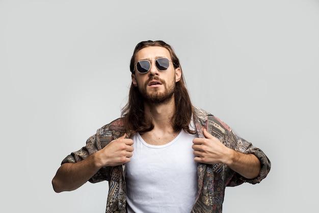 Brutaler tyrann mit langen haaren in dunkler sonnenbrille glättet sein hemd, selbstbewusster stilvoller kerl auf weißem hintergrund, freier stil, lebensstil der menschen