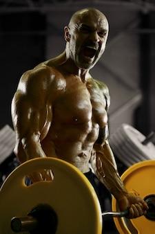 Brutaler und muskulöser starker bodybuilder athletischer mann, der beim training im fitnessstudio muskeln aufpumpt
