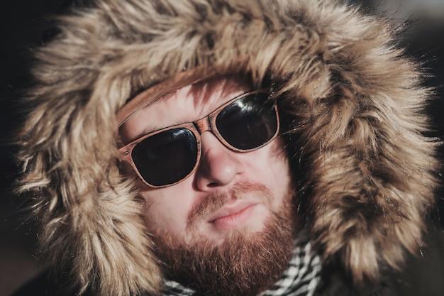 Brutales gesicht eines mannes mit bartstoppeln und fellkapuze im winter