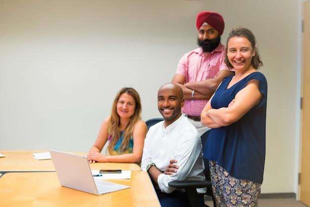 Bubsiness-team gebildet durch verschiedene ethniken im büro mit laptop