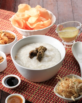 Bubur ayam oder indonesischer reisbrei mit geschreddertem hühnchen. serviert mit kerukpuk (cracker), sojasauce, gebratener sojabohne und sambal