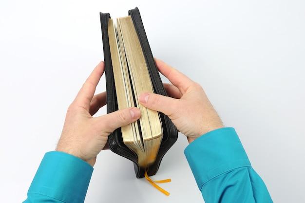 Buch der bibel in den händen auf weiß
