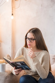 Buch der jungen Frau ernst beim Sitzen auf Sofa