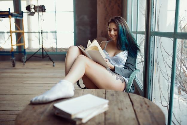 Buch der jungen frau lese, das nahe fenster sitzt