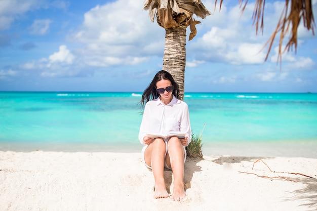 Buch der jungen frau lesewährend des tropischen weißen strandes