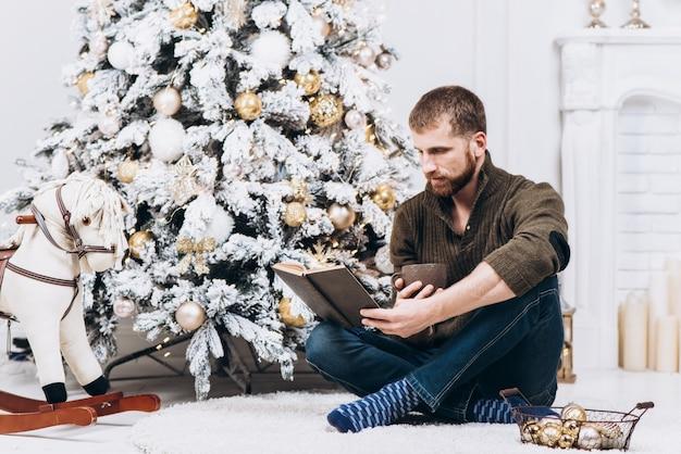 Buch des älteren mannes lese nahe dem verzierten weihnachtsbaum am weihnachtsabend