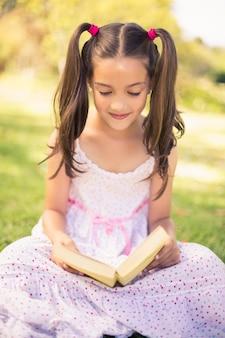Buch des jungen mädchens lesein park