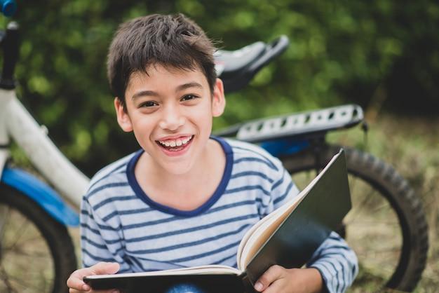 Buch des kleinen jungen lese, das mit fahrrad im park sitzt