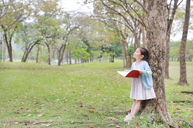 Buch des kleinen mädchens leseim parkmageres gegen baum mit oben schauen.