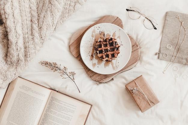 Buch, essen und andere dinge auf dem bettlaken
