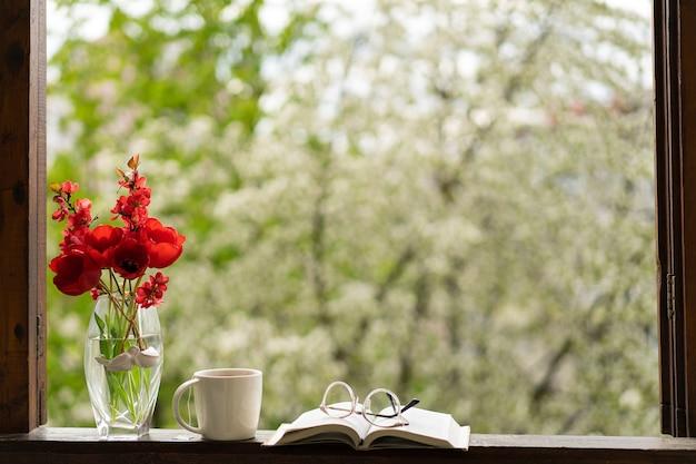 Buch, gläser, tasse tee und rote tulpen auf einem holzfenster