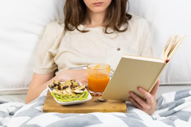 Buch im bett lesen und frühstücken