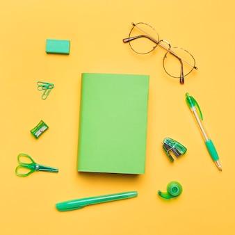 Buch in farbigem umschlag, umgeben von grünem schulmaterial