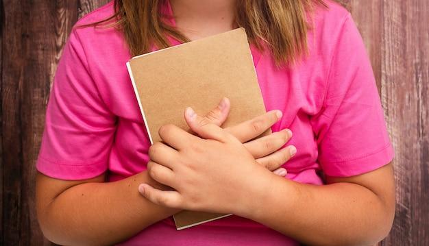Buch in weiblichen kinderhänden auf holzuntergrund