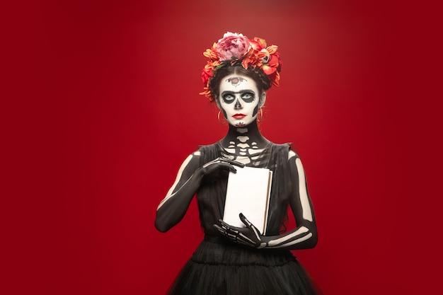 Buch. junges mädchen wie santa muerte saint death oder sugar skull mit hellem make-up. porträt auf rotem studiohintergrund isoliert. feiern von halloween oder tag der toten. exemplar auf dem cover.