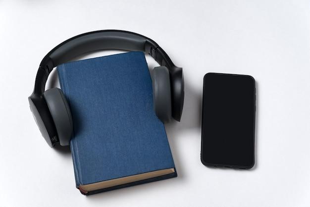 Buch, kopfhörer und telefon auf weißem hintergrund. hören sie bücher auf ihrem handy. hörbuchkonzept.