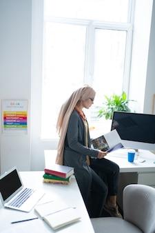 Buch lesen. junge muslimische lehrerin mit hijab sitzt in der nähe des fensters und liest ein buch