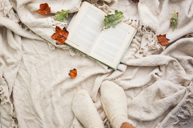 Buch liegt auf einem beigen wollplaid. herbstgefallenes laub und beine mit gestrickten weißen wollsocken