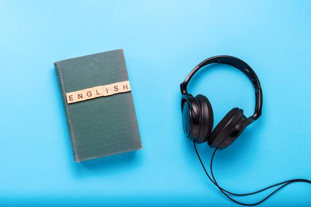 Buch mit einem blauen umschlag mit text englisch und schwarzen kopfhörern auf einem blauen hintergrund. konzept von hörbüchern, selbstbildung und selbständigem englischlernen. flache lage, draufsicht