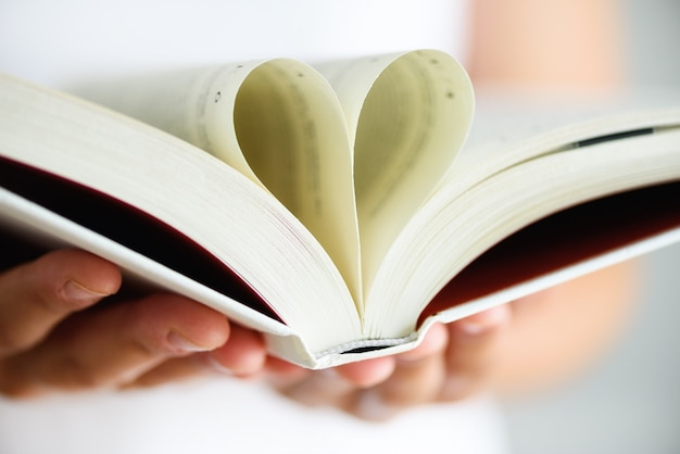 Buch mit geöffneten seiten und form des herzens in mädchenhänden.