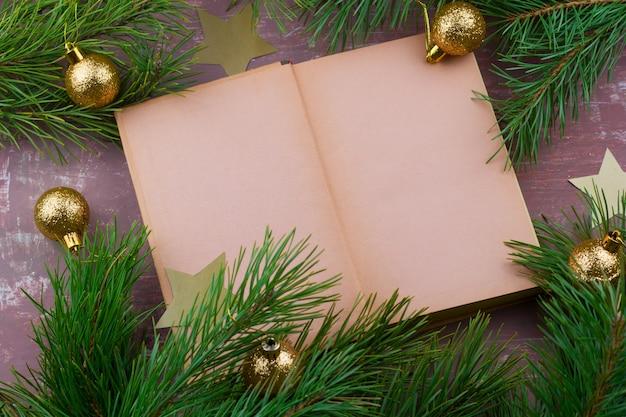 Buch mit leeren papierbögen und tannenzweigen mit goldenen weihnachtskugeln