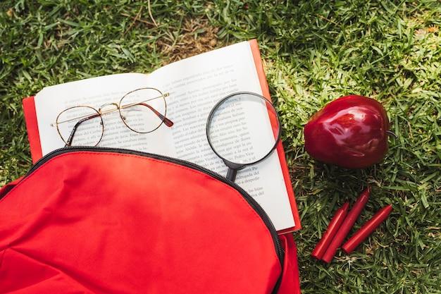 Buch mit optischen geräten in der nähe von rucksack und apfel