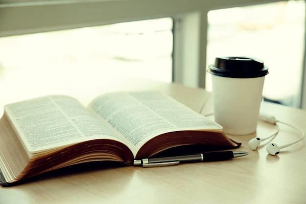 Buch mit tasse kaffee aufschlagen