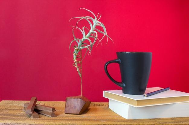 Buch mit tasse tee, schokolade koffer und pflanze auf holzuntergrund